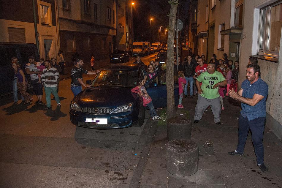 Ночью жители-румыны танцуют на улице, акустическая система в машине гремит громкой музыкой